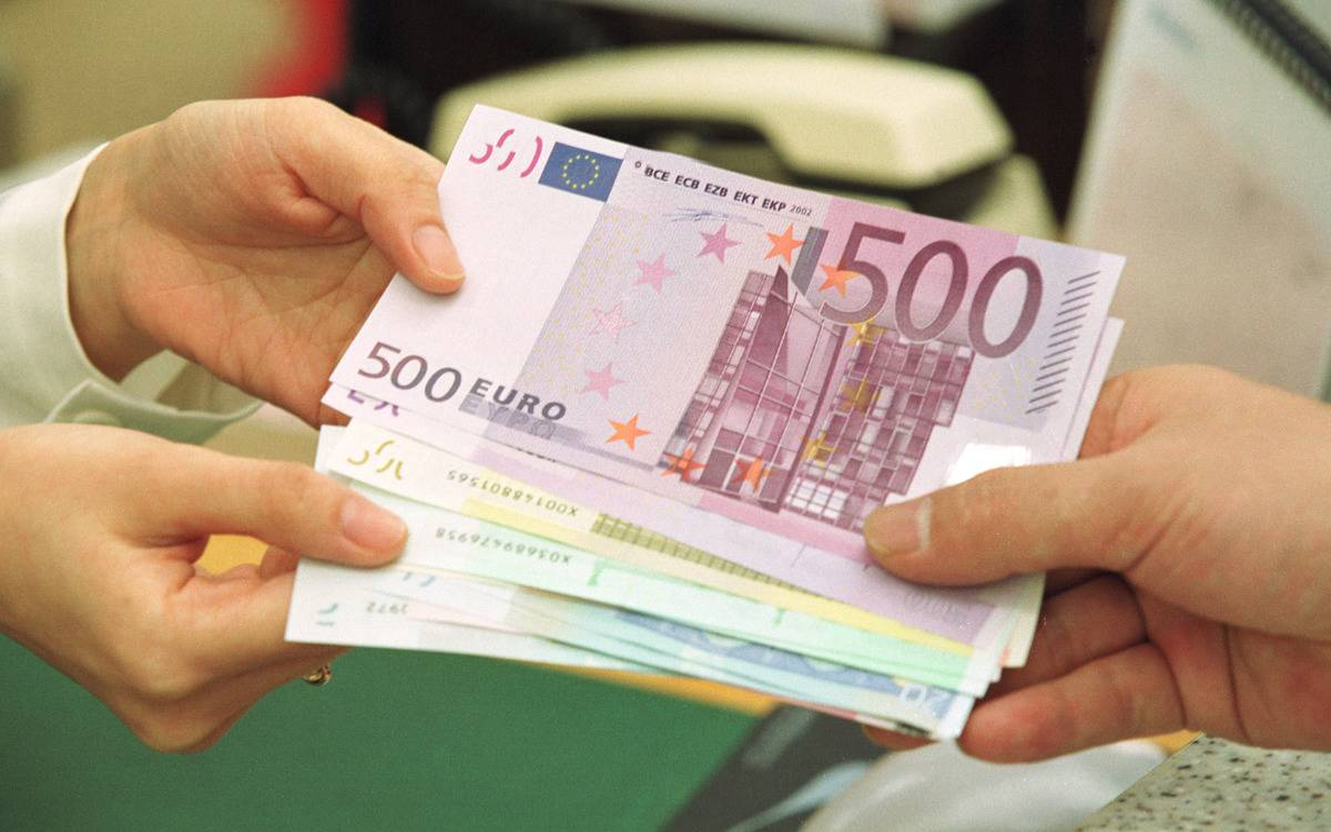 A person hands several hundred euros to another person.