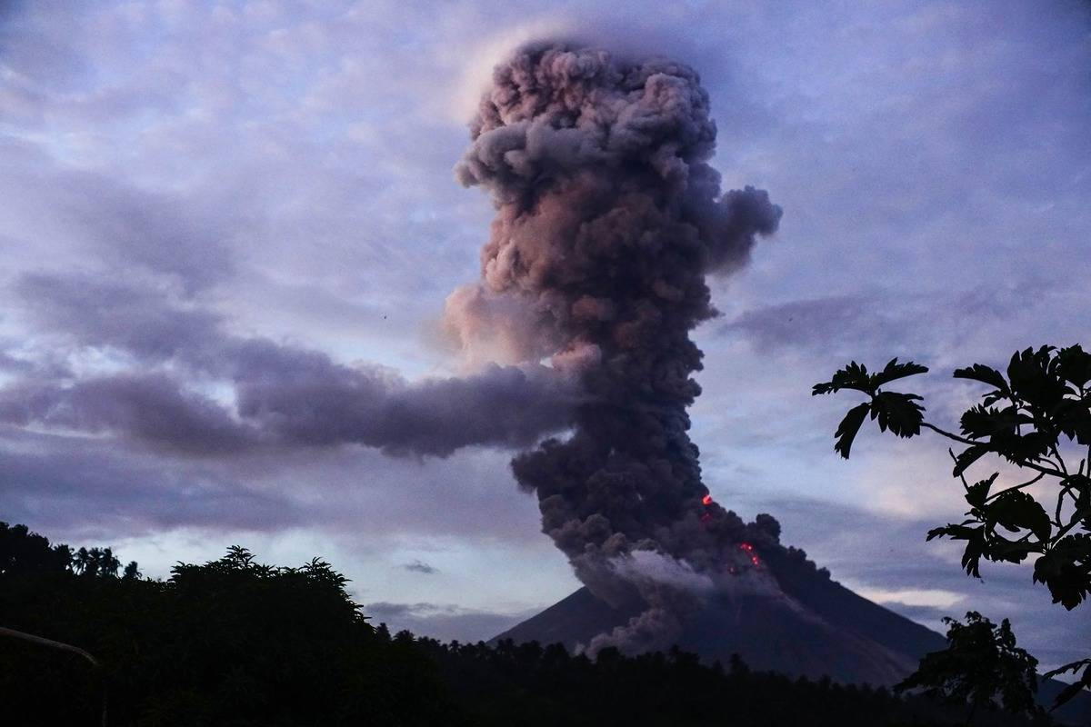 A volcano erupts and launches a lot of smoke into the sky.