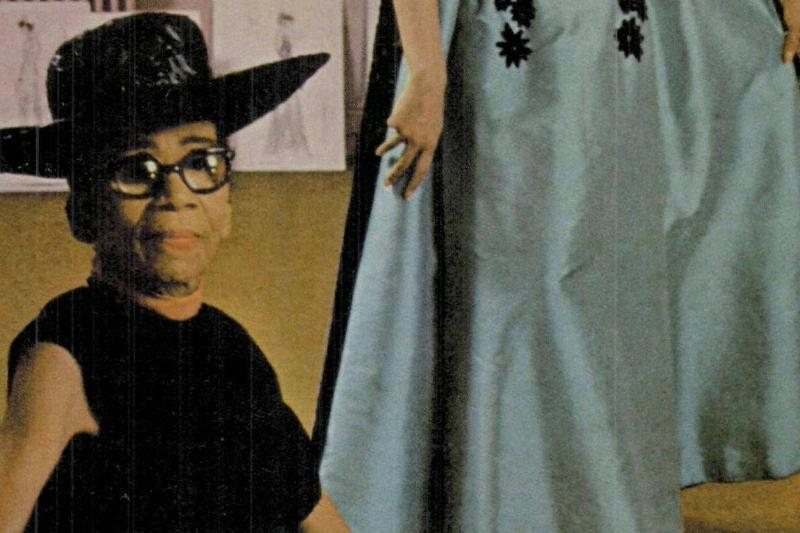 Anne Lowe sits in front of one of her dresses.