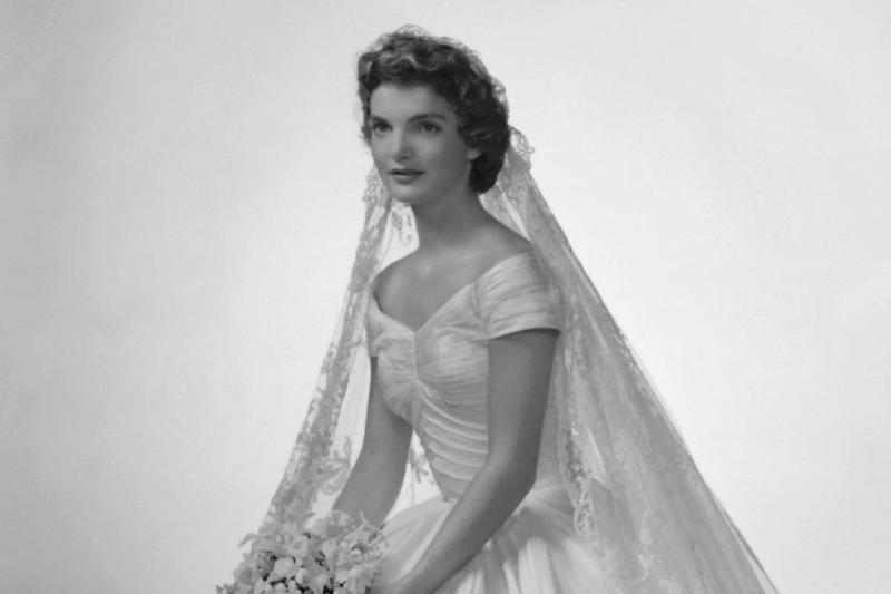 Jackie Bouvier sits in her ballgown wedding dress.