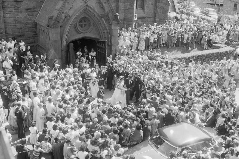 John and Jackie Kennedy walk out of the church through the crowds to get to their car.