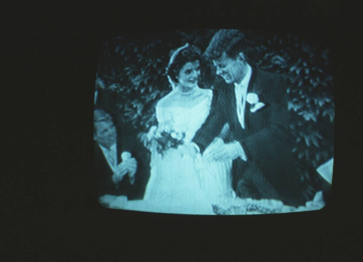 In 1977, a TV broadcasts a replay of the Kennedy wedding.