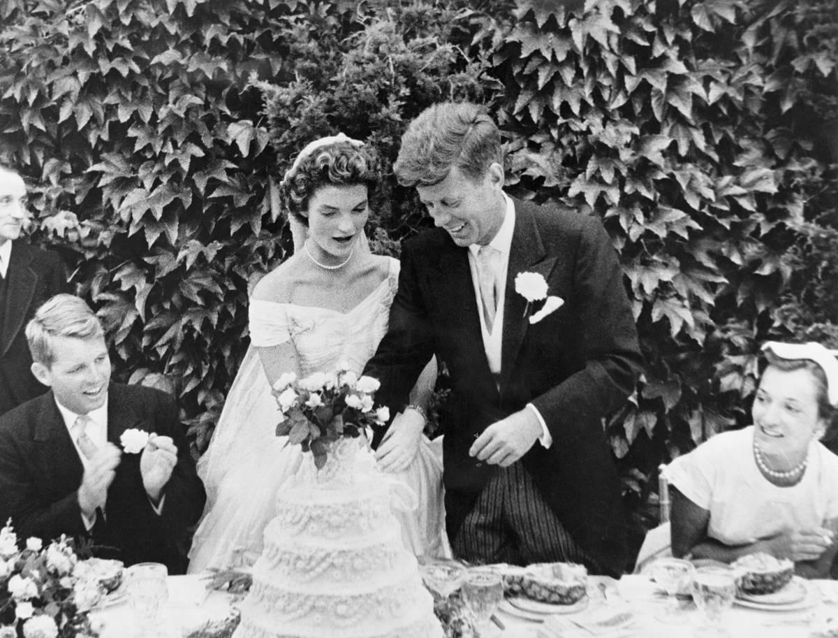 John F. and Jackie Kennedy cut their wedding cake during their reception.