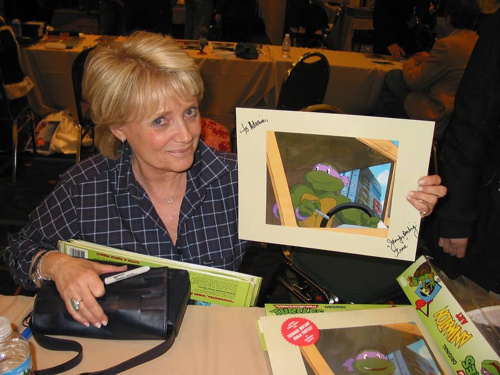 jennifer darling holding a signed poster of the teenage mutant ninja turtles