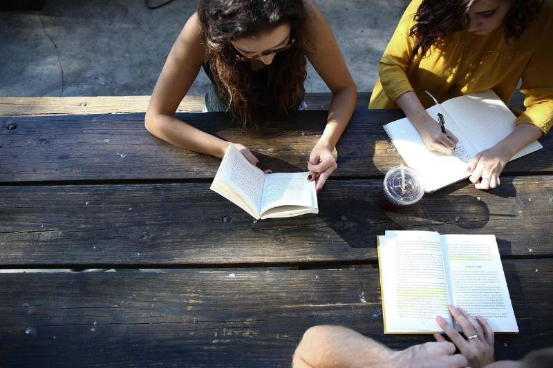 A group of people study at an outdoor table.