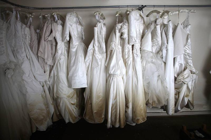 After a flood, hanging wedding dresses are brown and decayed at the bottom.
