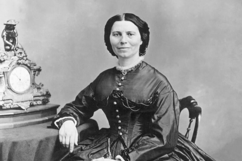Clara Barton, under President Abraham Lincoln's charge for sending supplies to civil war soldiers, holds a pair of gloves next to a table and clock.