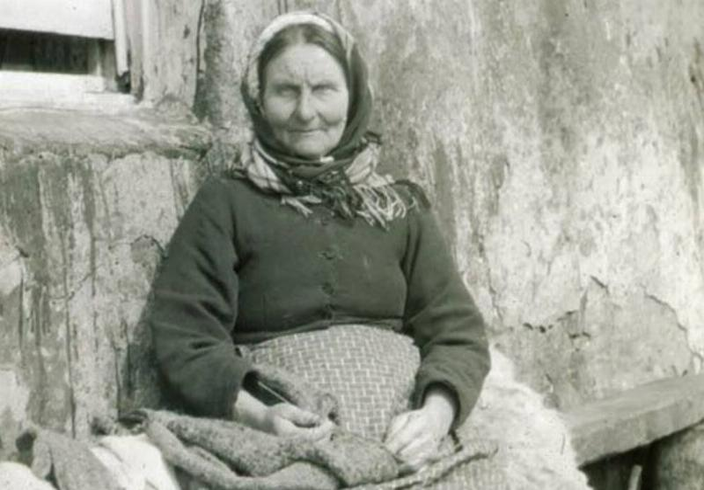 An elderly woman leans against a wall on Hirta.