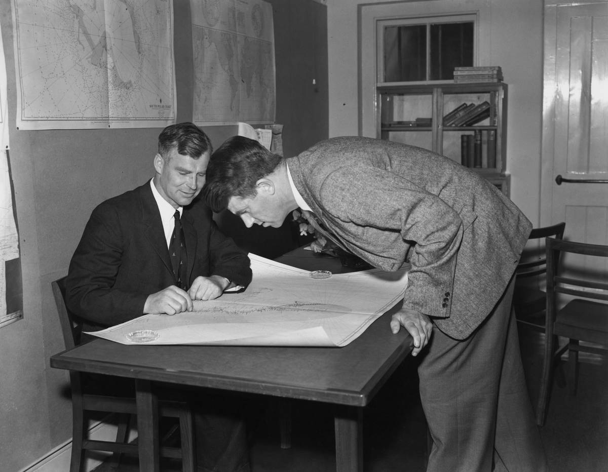 Men study a map together in 1955.