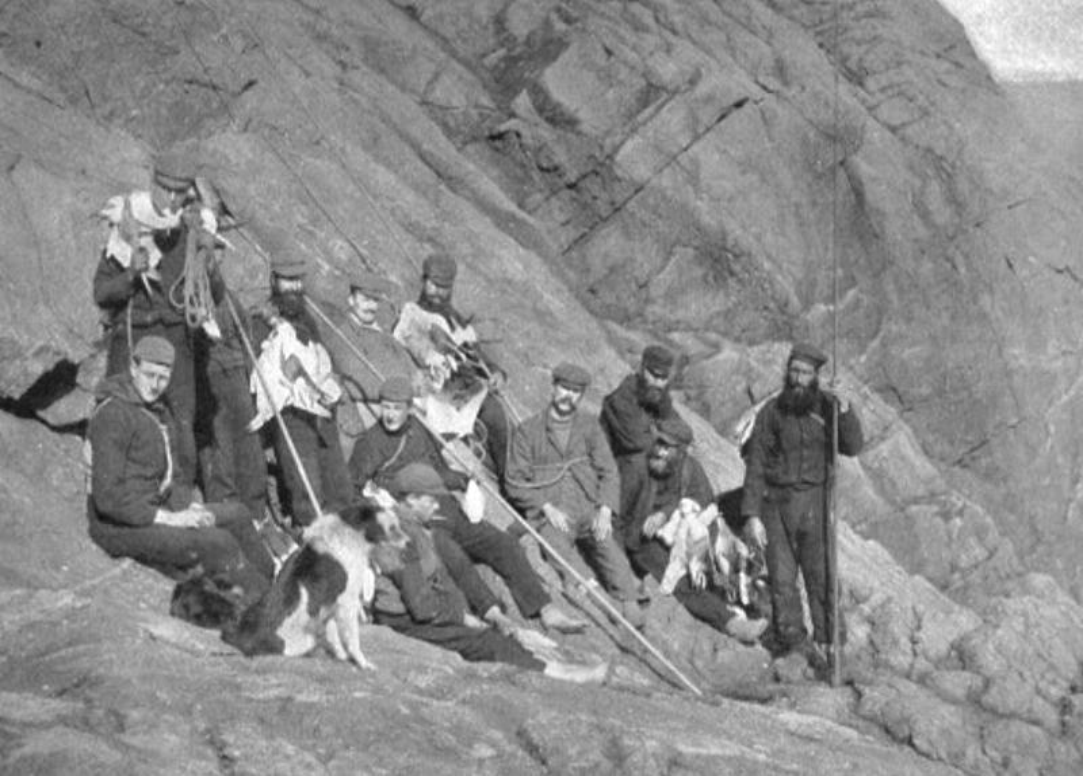 Multiple men stand together on a cliffside in St. Kilda.