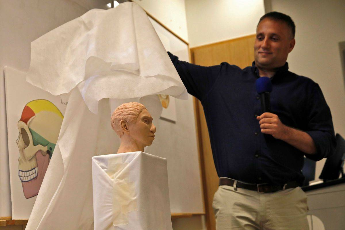 A professor reveals a 3D model of the head of an ancient human, the Denisovan.