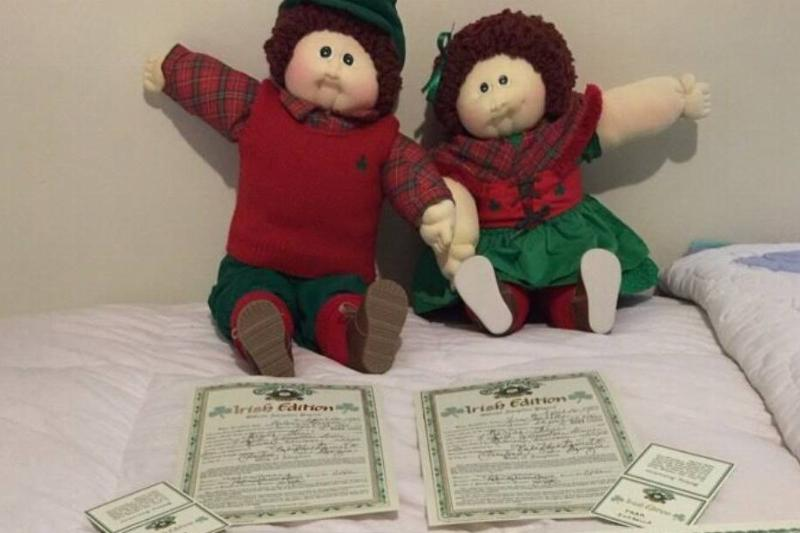 The Cabbage Patch Irish Fraternal Twins are propped up near their adoption papers.
