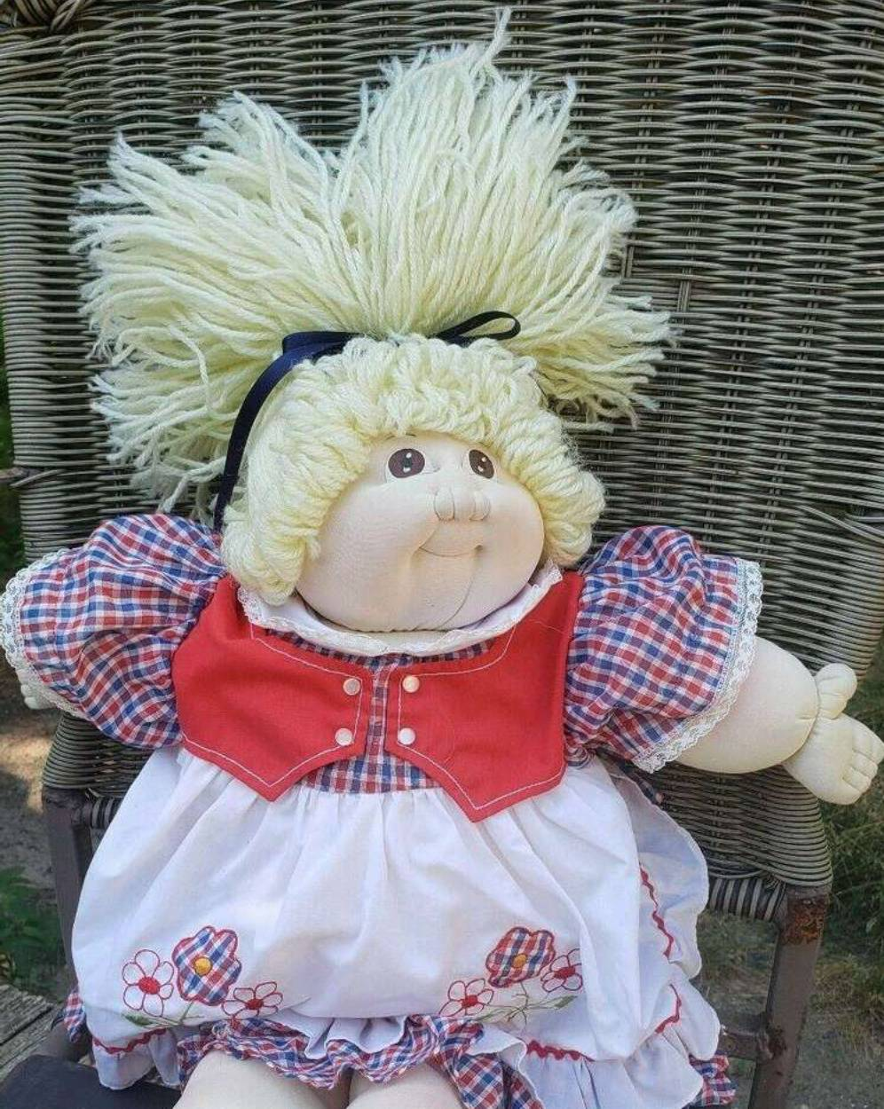 A blonde Little People Doll sits on a wicker chair.