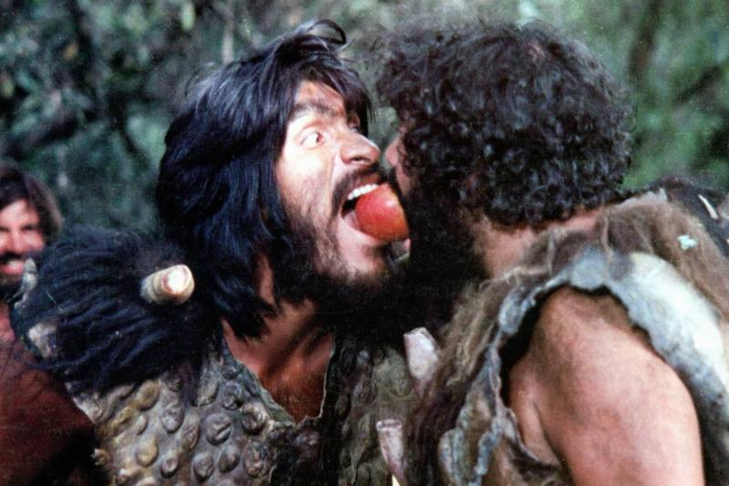 Two Neanderthals bite the same apple in the 1981 movie