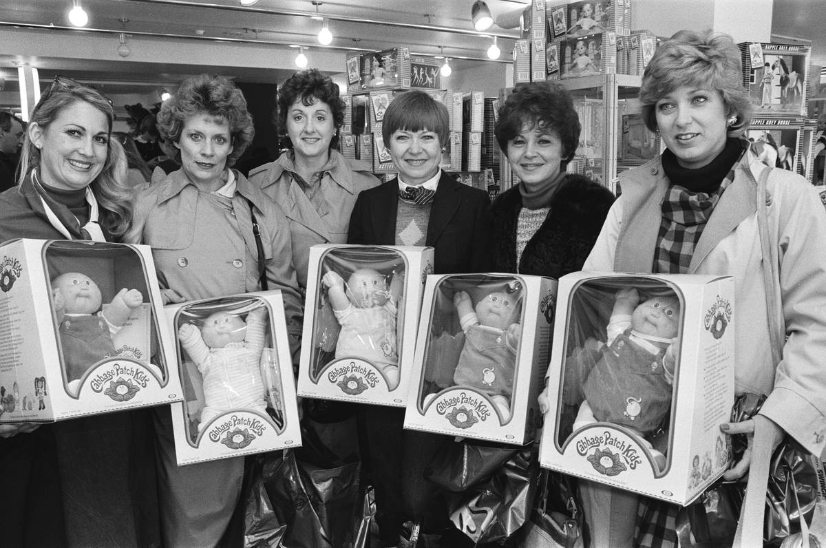 Women hold boxes of Cabbage Patch Kids, 1983.