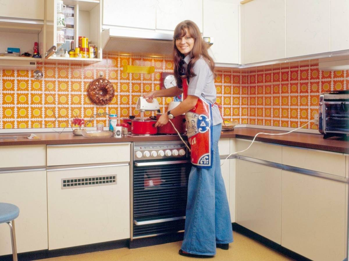 A woman smiles as she bakes in her orange 1976 kitchen.