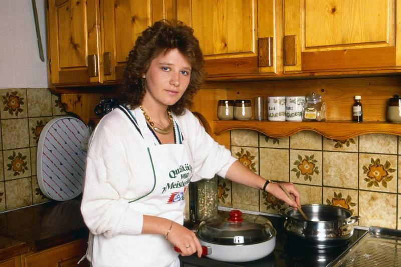 A woman cooks at her stove, 1989.