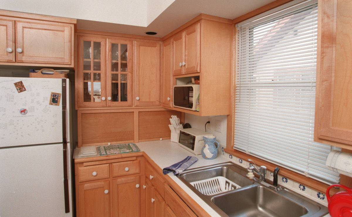A kitchen in the 1990s has cabinets of pale wood and white granite countertops.
