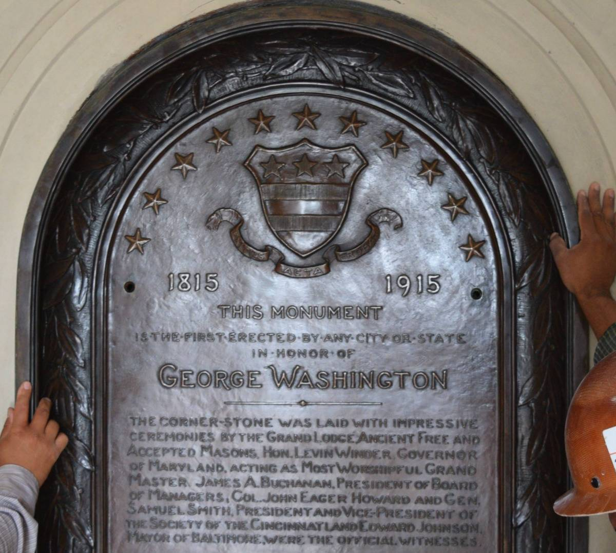 The original plaque from 1915 is held up.
