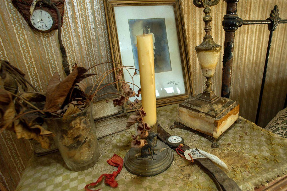 Hubert Rochereau's bedside table contains dried flowers, a candle, a watch, and a framed portrait.
