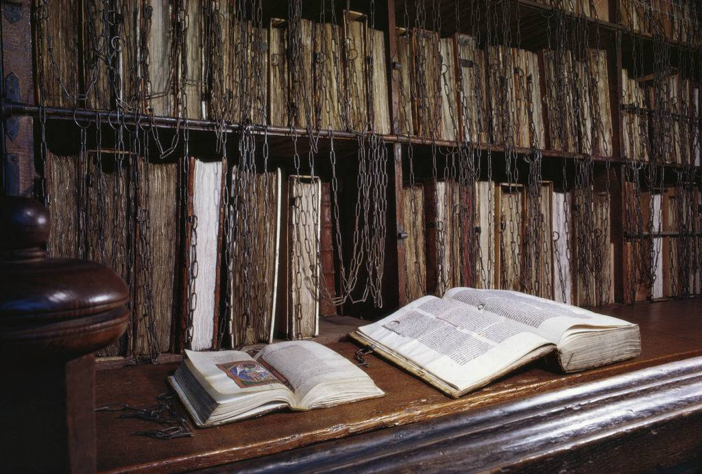 Antique books old manuscripts and bound volumes are chained to lecterns in the chained library of Hereford Cathedral