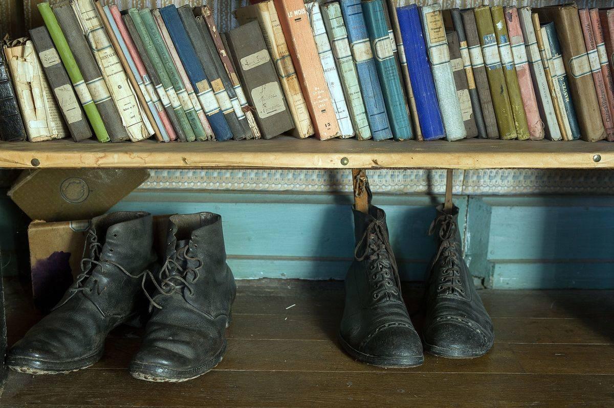 Hubert Rochereau's military boots are on the bottom shelf of a bookshelf.