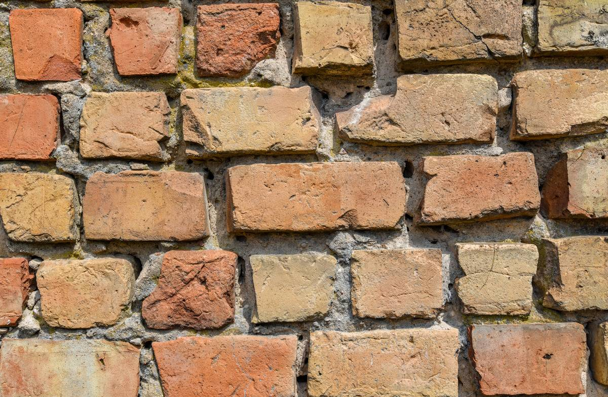 A close-up photo shows a weathered brick wall.