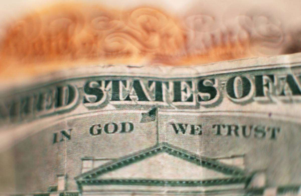 A close-up of a U.S. $20 bill shows the motto