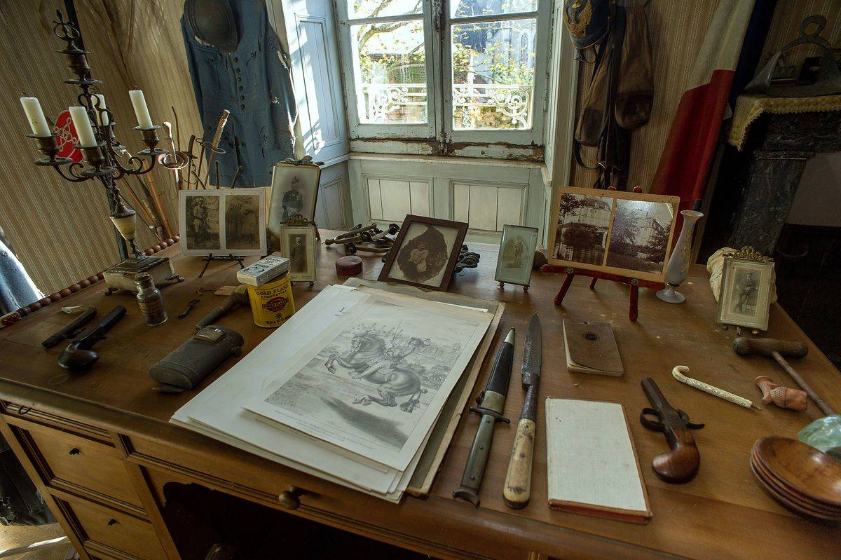 Hubert Rochereau's desk contains photos, a drawing, a notebook, knives, pistols, and cigarettes.
