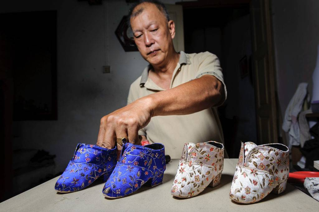 a man making special shoes for bound feet