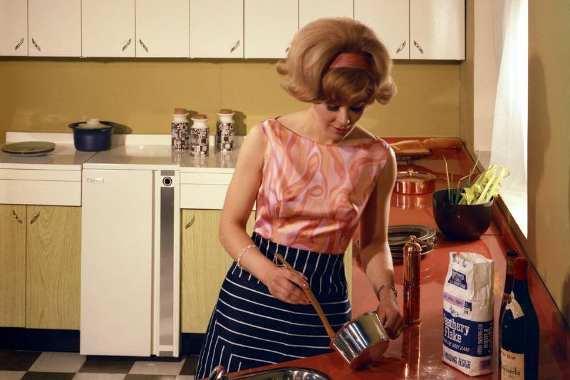 In 1966, a woman cooks in a kitchen with golden walls, a stainless steel sink, and red countertops.
