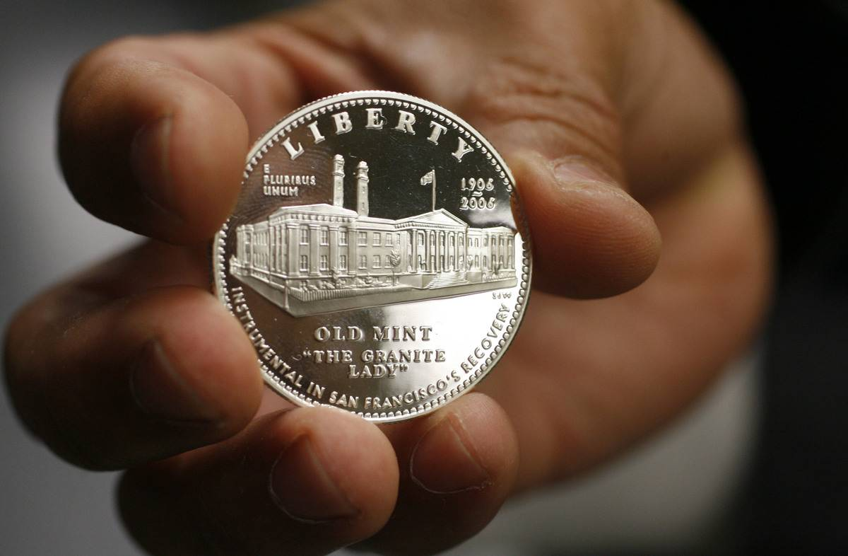 A person holds an Old Mint silver coin.