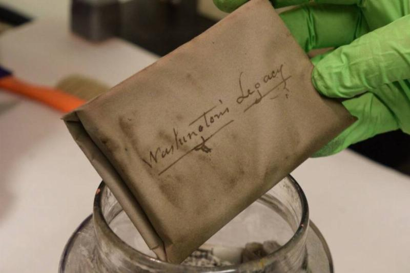 A person picks up a copy of George Washington's inaugural address from a time capsule jar.