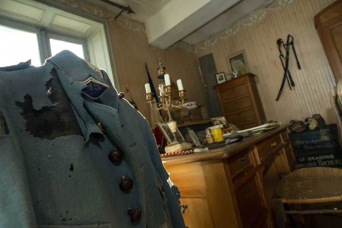 Hubert Rochereau's military jacket and desk are seen in his room.