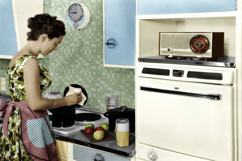 A woman cleans her kitchen appliances, 1959.