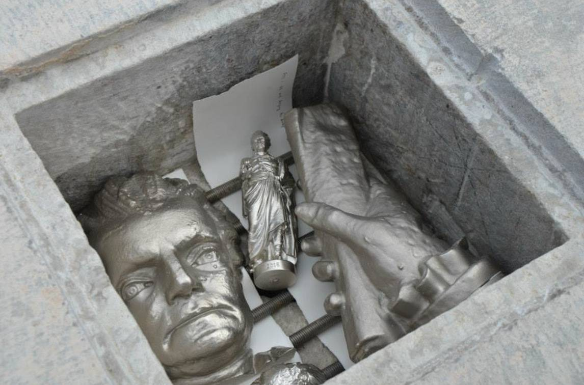 A new cement time capsule includes metal recreations of statues.