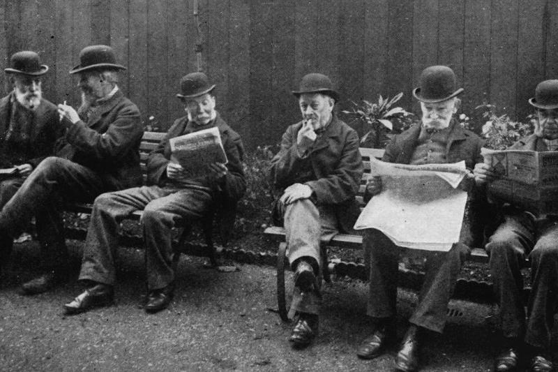 Men read newspapers on a public bench in 1903.