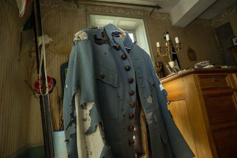 Hubert Rochereau's moth-eaten military jacket hangs on a hook.
