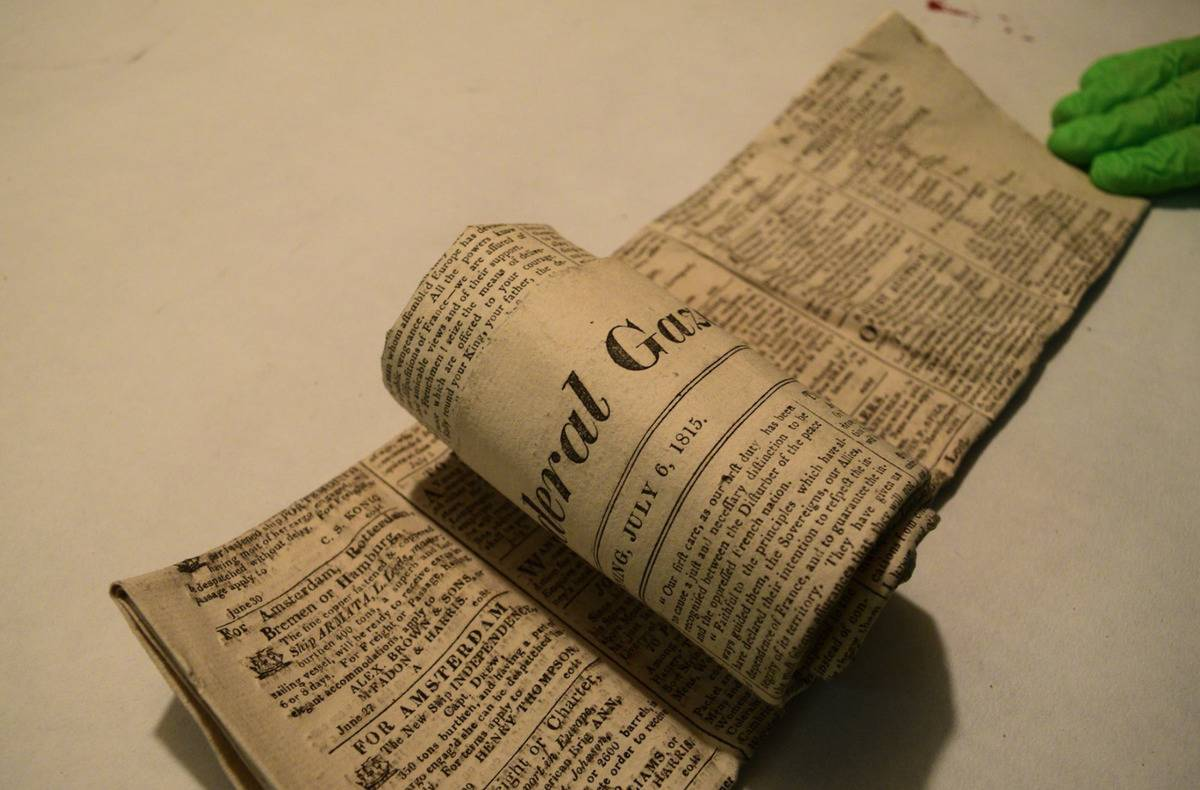 An old Federal Gazette newspaper is rolled out on a table.
