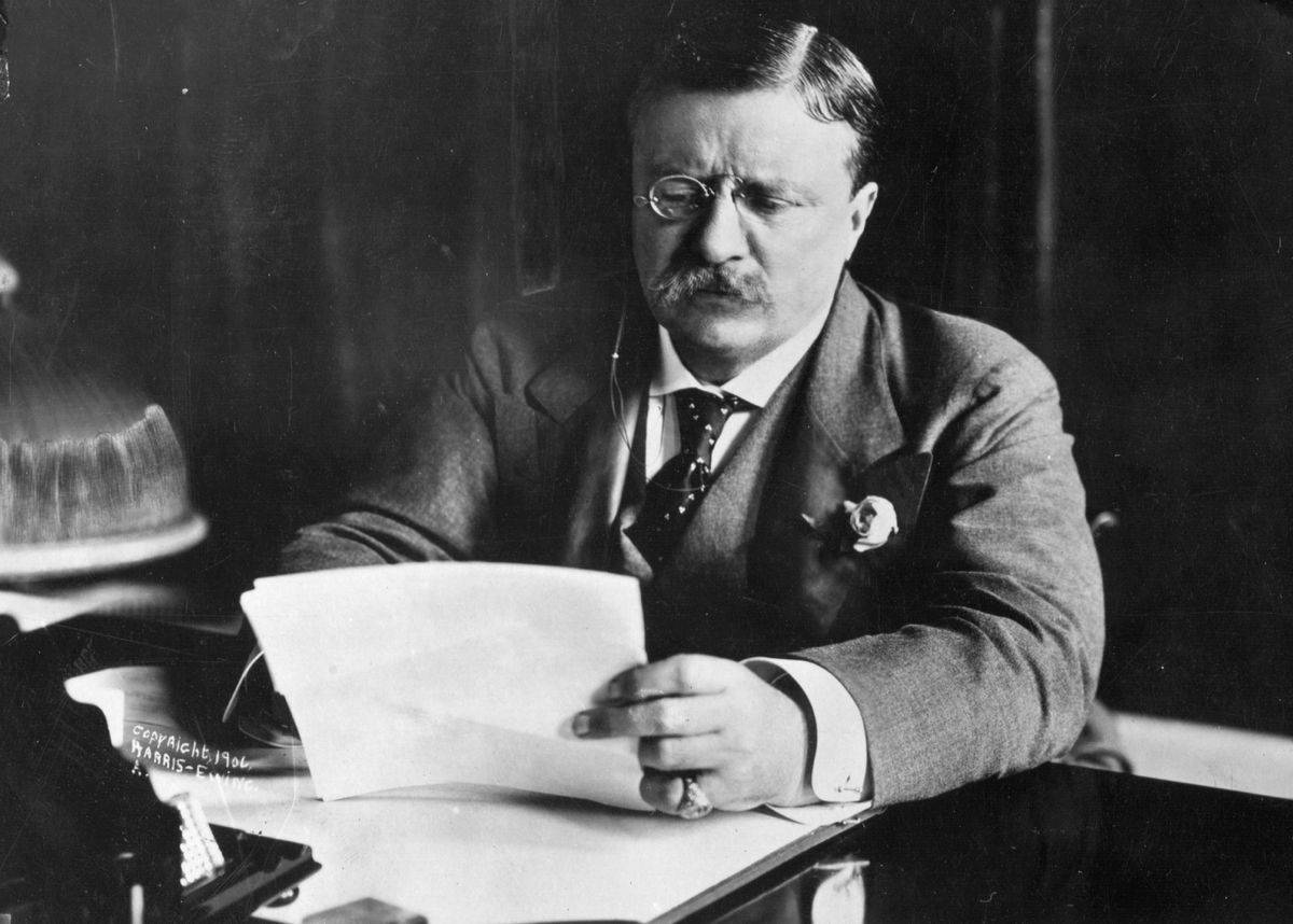 In 1905, Roosevelt sits at his desk and reads a letter.