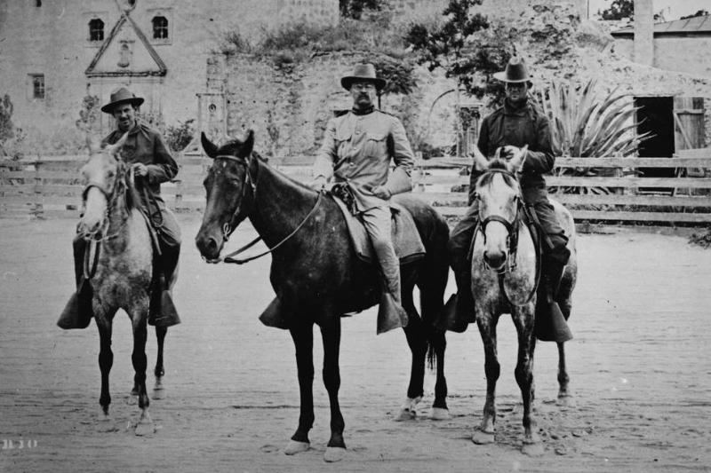 Theodore Roosevelt is on a horse with the Rough Riders in San Antonio.