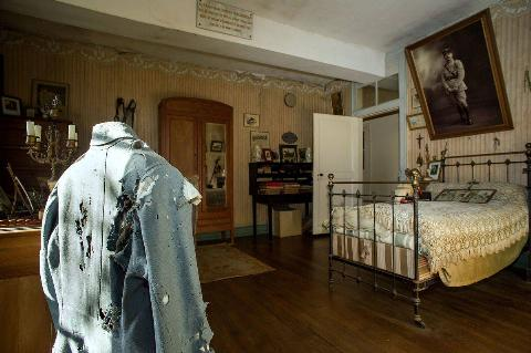 A photo shows the preserved bedroom of Hubert Rochereau, with his military jacket, bed, and portrait hanging.