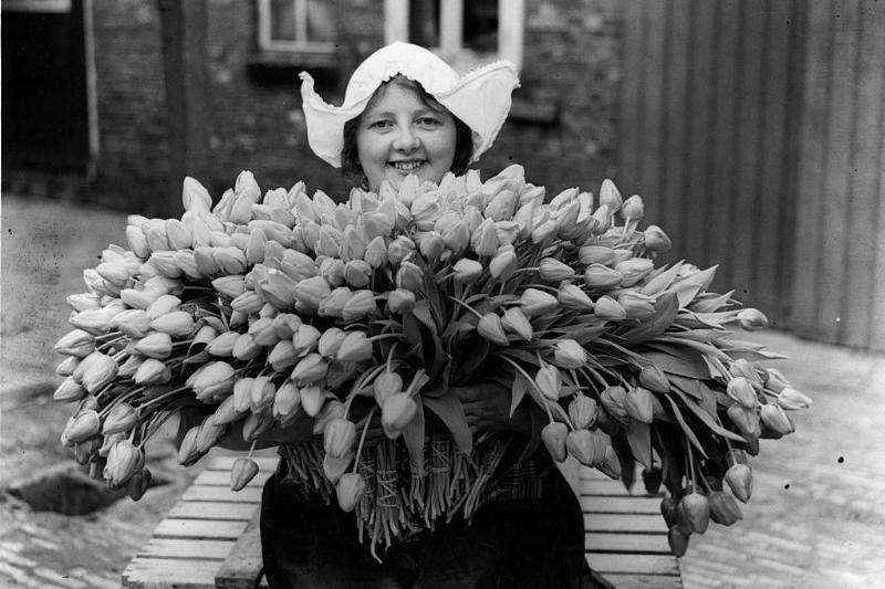 a Dutch woman holding tulips in black and white