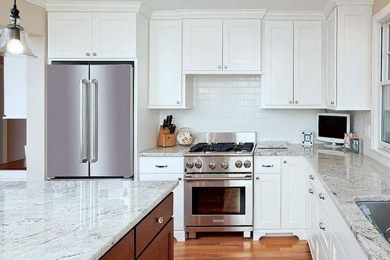 A kitchen from the 2010s has white cabinets and quartz marble countertops.