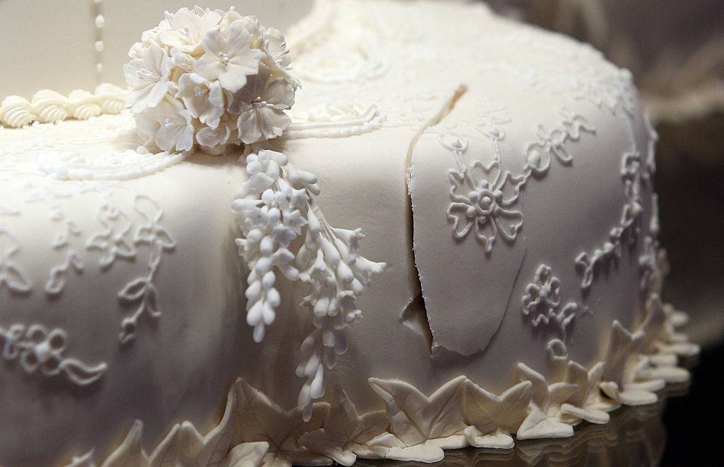 a white wedding cake with a cut on the side