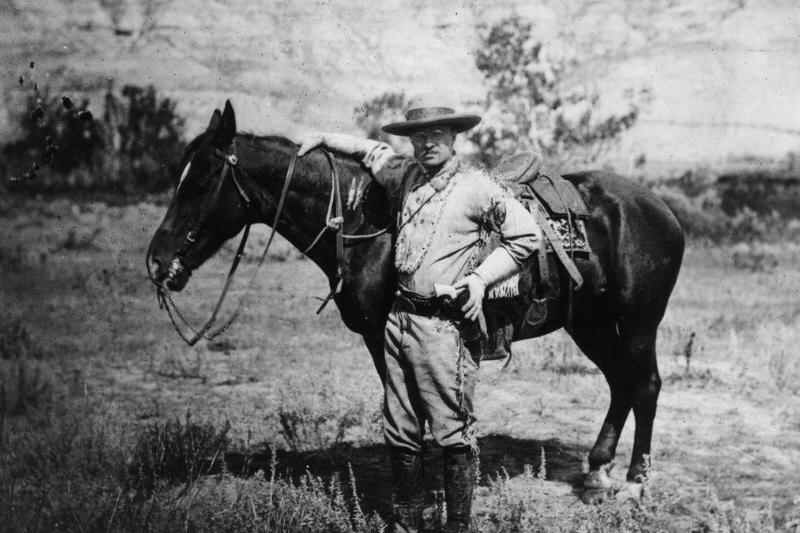 Roosevelt stands next to his horse.