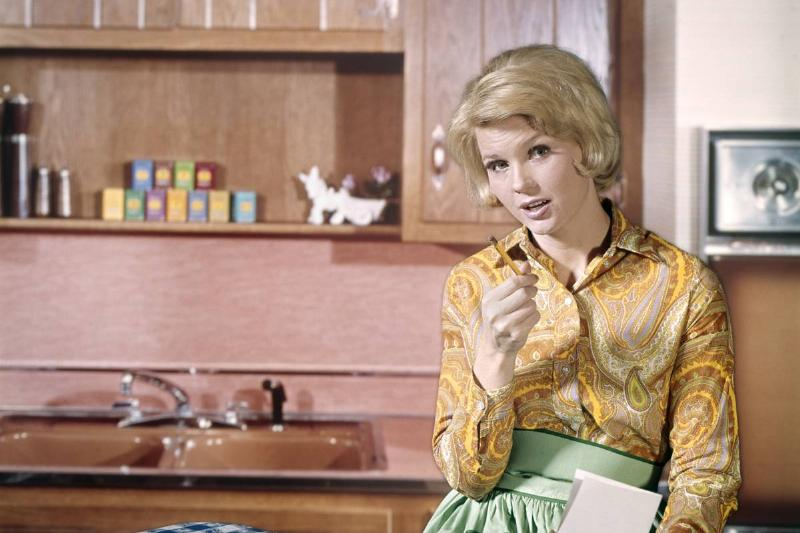In the 1960s, a woman sits in her kitchen and thinks about a grocery list.