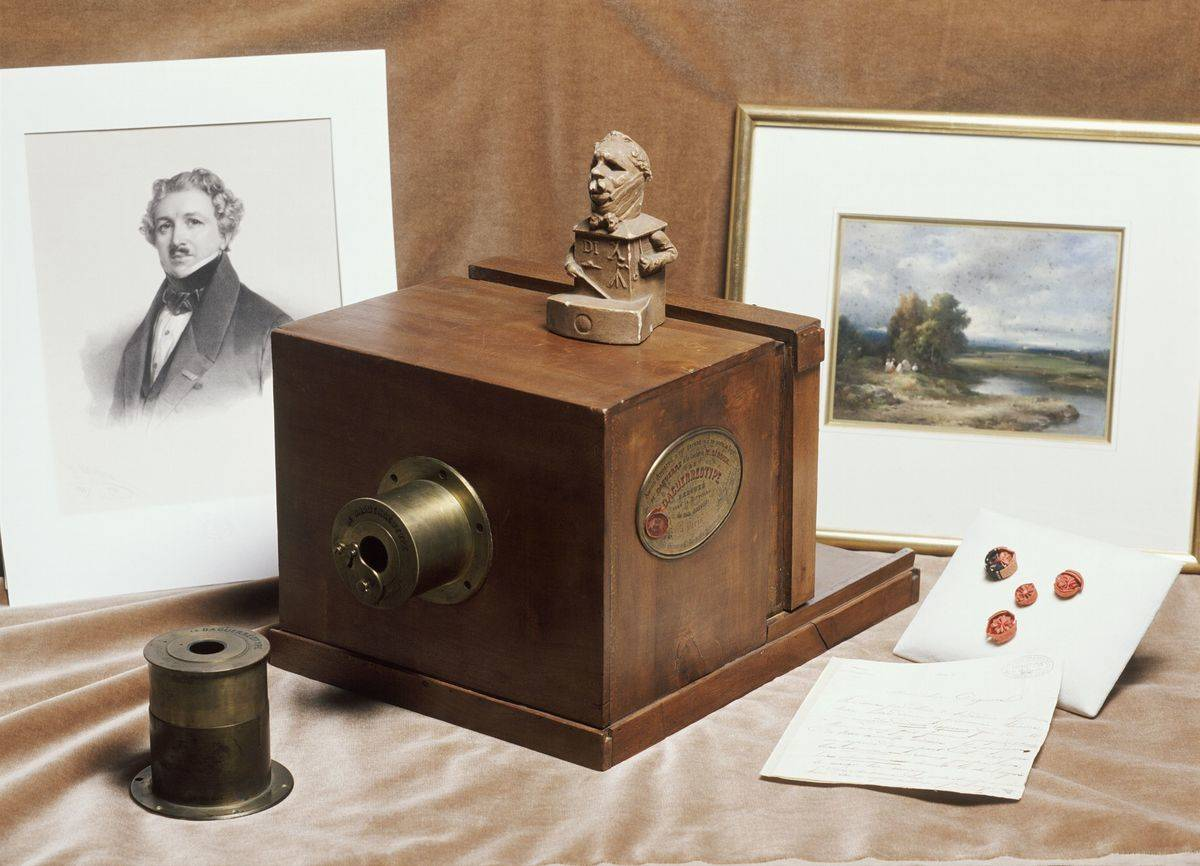 A Daguerreotype camera is in front of two pictures, 1839.
