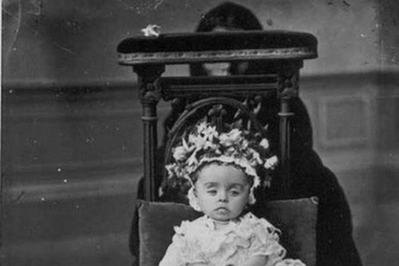 A baby's mother hides behind the baby's chair.