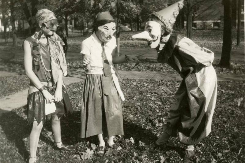 Three girls wearing masks and in costume stand outside and converse with each other